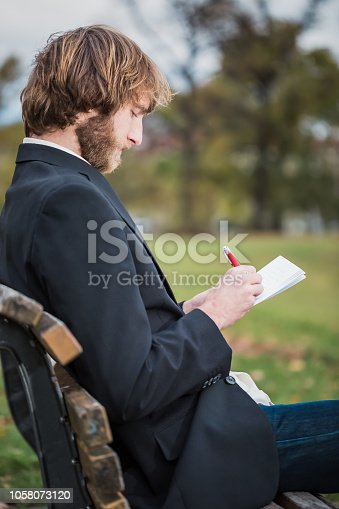 1175668510 istock photo Business man is sitting in the park and is writing. 1058073120