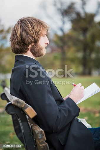 1175668510 istock photo Business man is sitting in the park and is writing. 1058073140