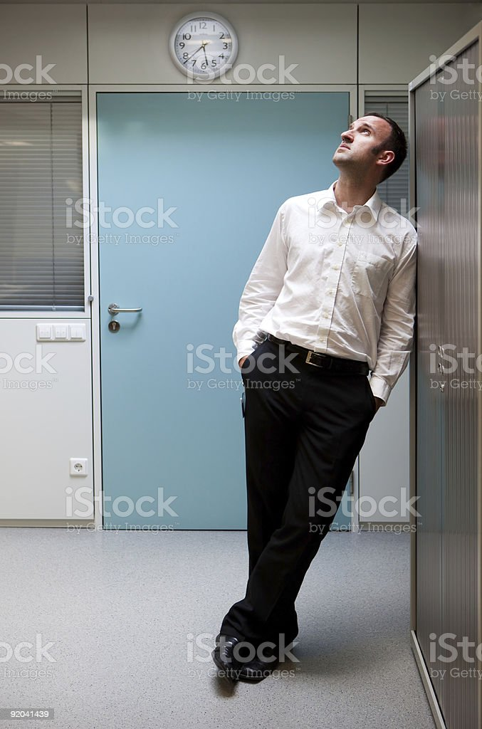 Business man is thinking in front of a clock royalty-free stock photo