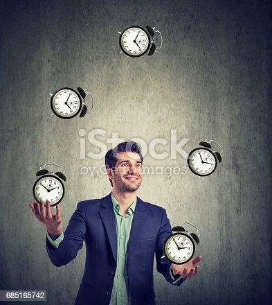 istock business man juggling his time alarm clocks 685165742