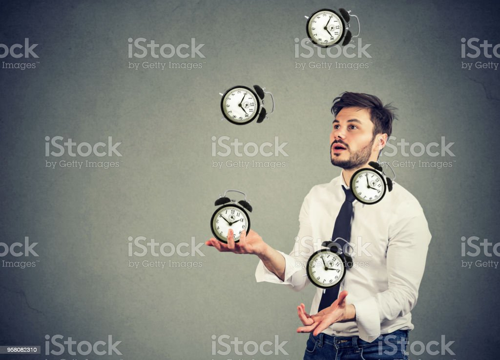 business man juggling his time alarm clocks stock photo