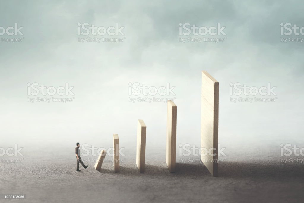 business man kick the first domino piece stock photo