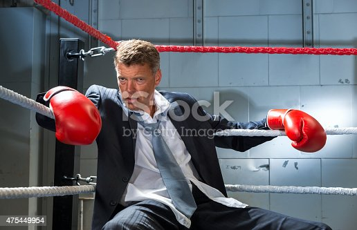 464164875 istock photo Business Man Knocked Out in corner of box ring 475449954