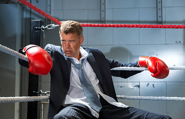 Business Man Knocked Out in corner of box ring stock photo