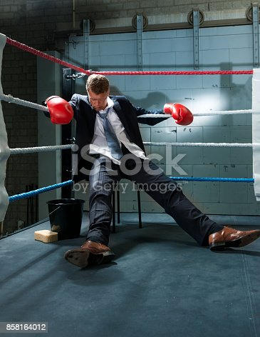 464164875 istock photo Business Man Knocked Out in corner of box ring 858164012