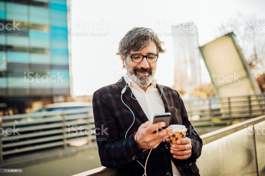 Older man using mobile phone and in-ear headphones while having a cup...