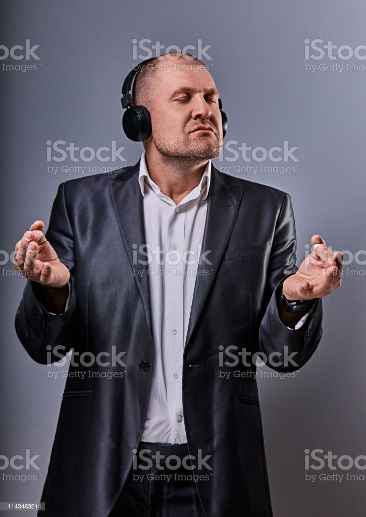 Business man listening the music in wireless earphone and trying relax he showing the hands yoga sign zen on grey studio background. Closeup - Royalty-free Actor Stock Photo