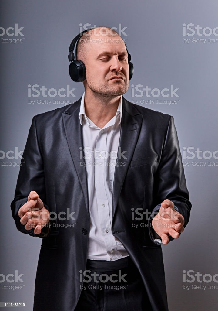 Business man listening the music in wireless earphone and trying relax he showing the hands yoga sign zen on grey studio background. Closeup royalty-free stock photo