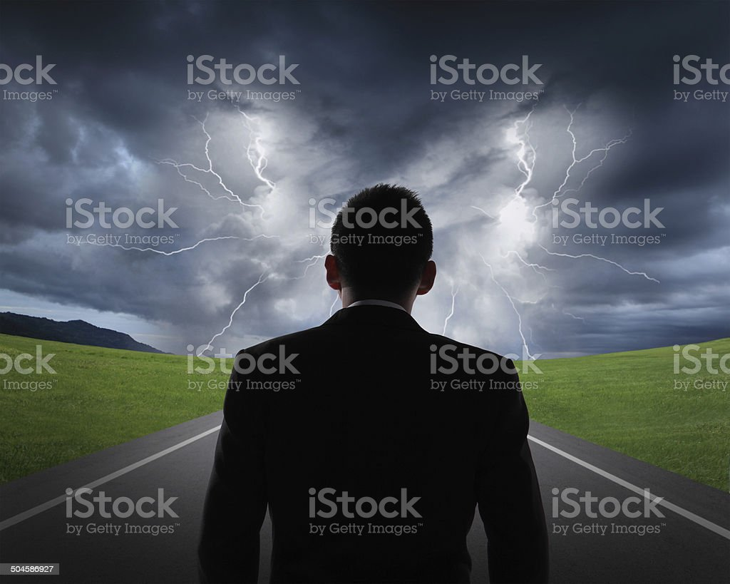 business man look rainstorm clouds and lightning stock photo