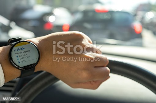 istock business man look smartwatch Leather watchbands black color circle front on left hand show agenda weekly meeting schedule notification when where and organize in car with traffic jam 865238224