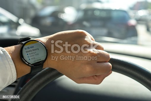 istock business man look smartwatch Leather watchbands black color circle front on left hand show agenda weekly meeting schedule notification when where and organize in car with traffic jam 865238304