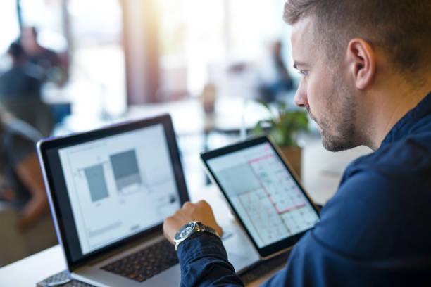 노트북 컴퓨터와 태블릿에서 프로젝트를 찾고 분석 하는 사업가. - 분석 보기 뉴스 사진 이미지