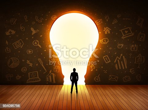istock Business man looking at bright light bulb in the wall 934095756