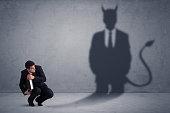 ビジネスマンの彼自身の悪魔悪魔影の概念を見て