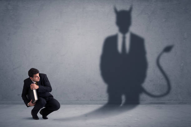 Business man looking at his own devil demon shadow concept stock photo