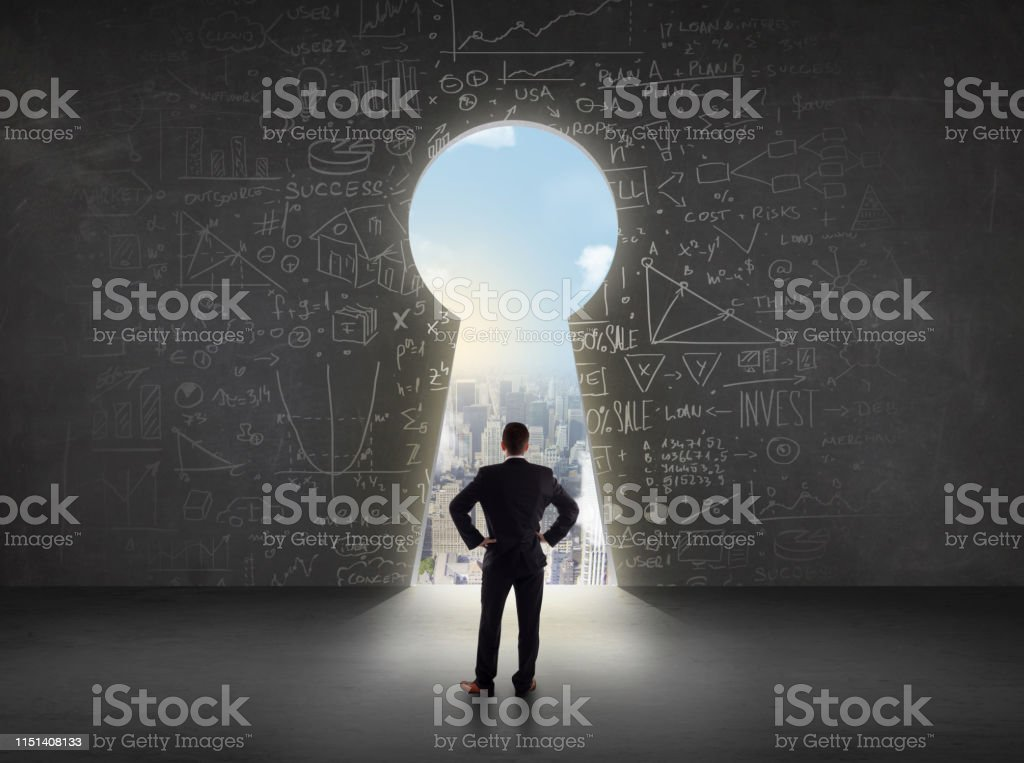Business man looking at keyhole with bright cityscape concept...