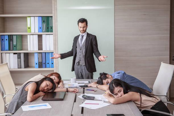 business-mann betrachtet man müde kollegen schlafen erschöpft von der harten arbeit in einem besprechungsraum - traum team stock-fotos und bilder