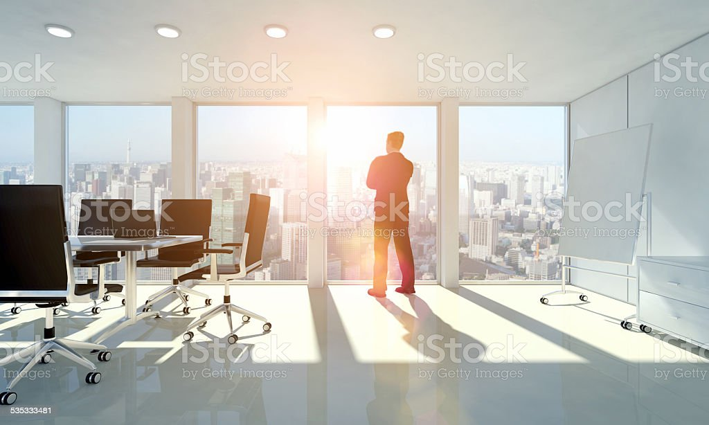 Business man looking through window meditating about the future stock photo