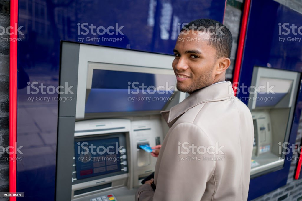 Business man making a cash withdrawal on an ATM stock photo