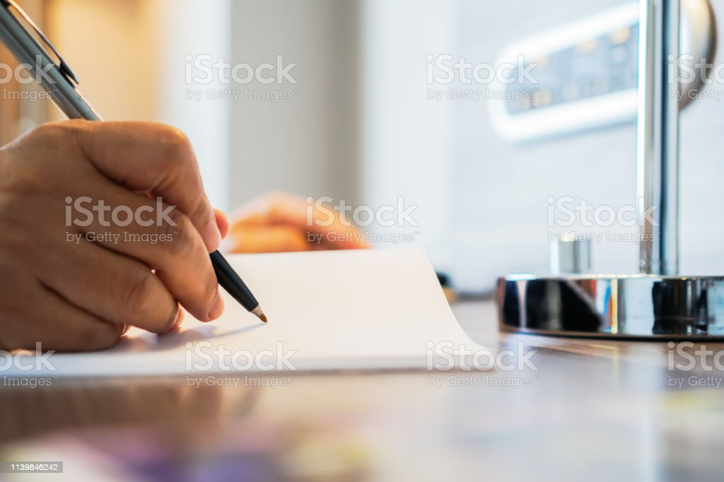 Business man Manager sitting hold pen for signing applicant filling documents reports papers company application form or registering claim on office. Document Report and business busy Concept stock photo