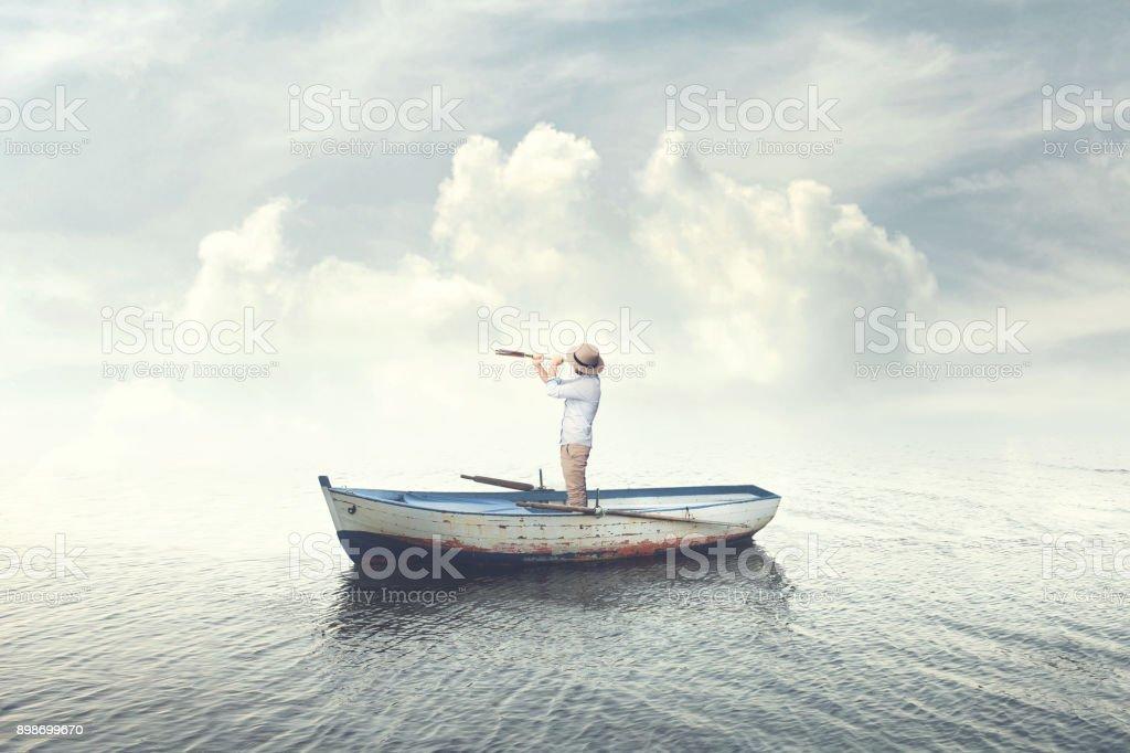 homme d'affaires sur un bateau je regarde l'avenir avec des jumelles photo libre de droits