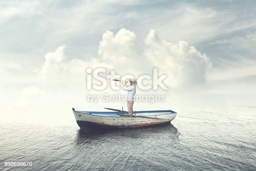business man on a boat watching the future with binoculars
