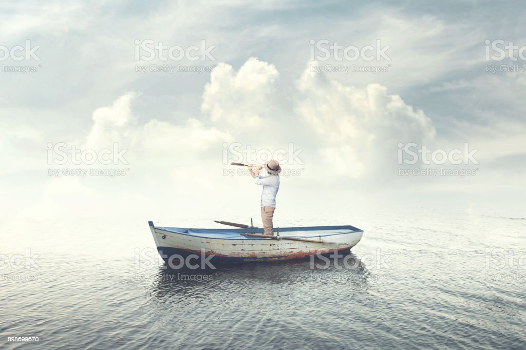business man on a boat watching the future with binoculars stock photo