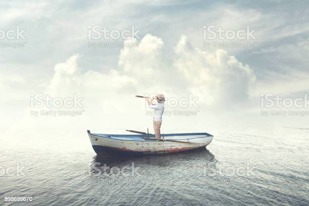 Photo of business man on a boat watching the future with binoculars