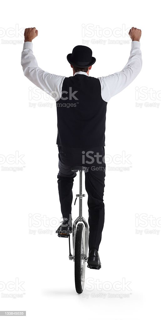 Business Man on a Unicycle Holding Arms Up stock photo