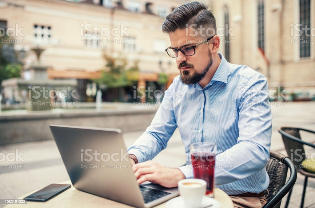 Young businessman sitting in a cafe drinking coffee and working with...