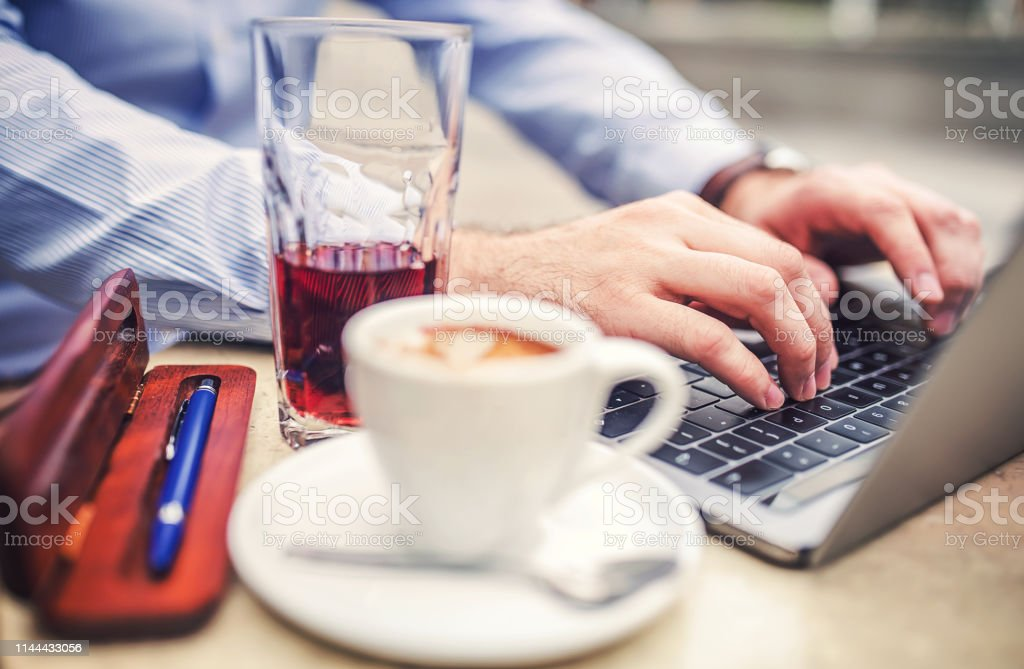 Businessman sitting in a cafe drinking coffee and working with...