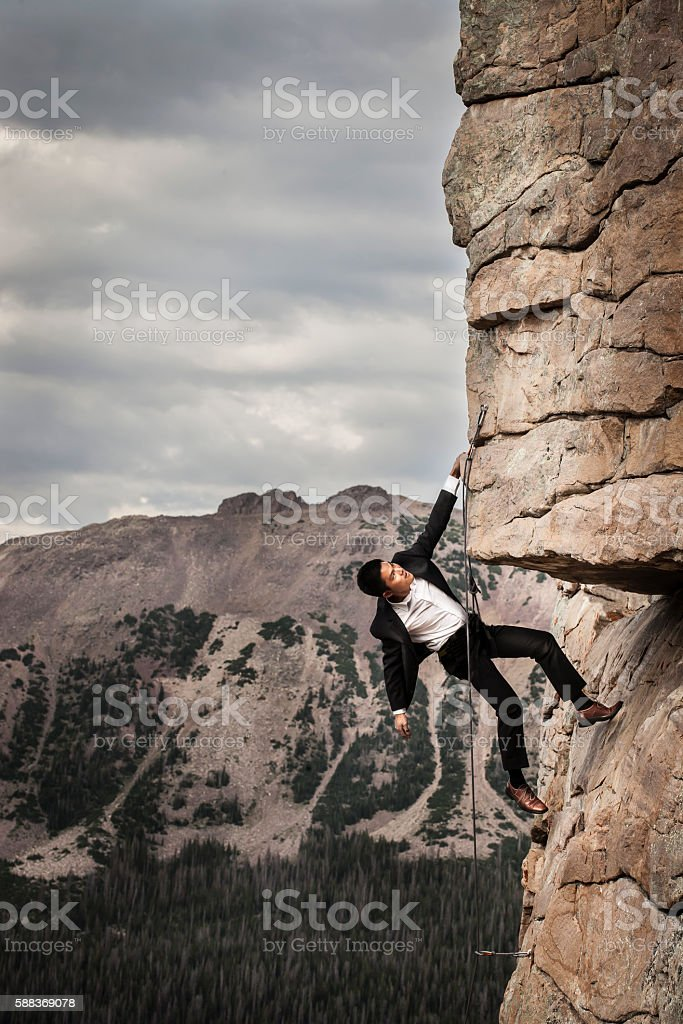 Business Man on Rock Face stock photo