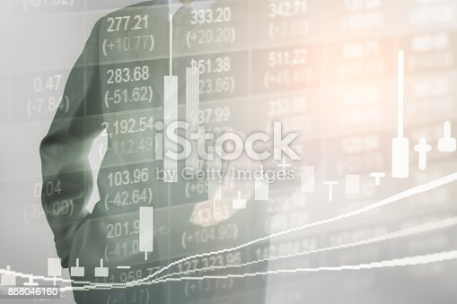 903982138istockphoto Business man on stock market financial trade indicator background. Man analysis stock market financial trade indices on LED. Double exposure of business man trade on stock market financial concept. 858046160
