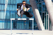 young business man with briefcase and sunshades running over hurdle
