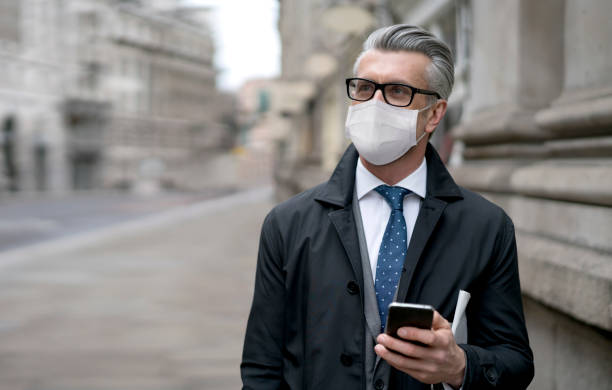 business man on the street wearing a facemask to avoid covid-19 and using app on his cell phone - businessman covid mask foto e immagini stock