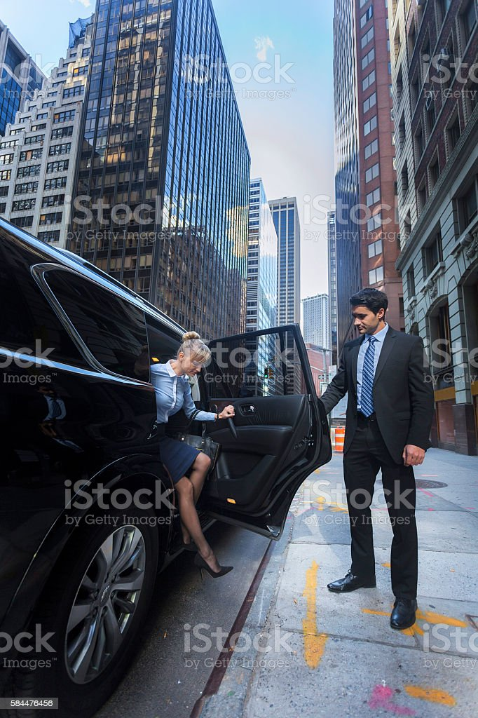 Business man opening car door for woman stock photo