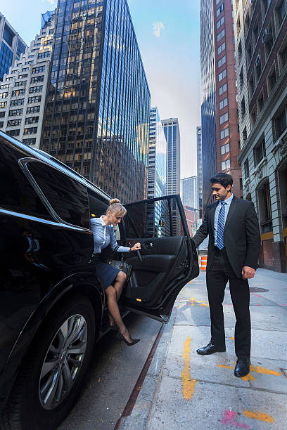 business man opening car door for woman - limousine service stock photos and pictures