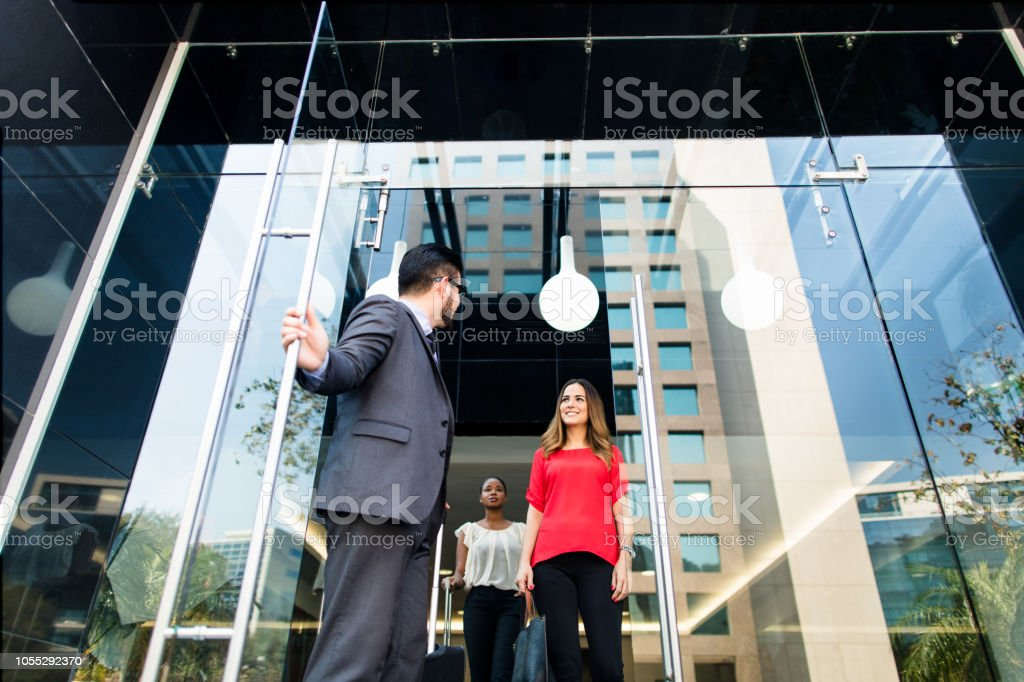 Business man opening door for partners stock photo