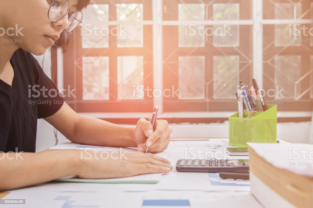 Business man or accountant in black shirt holding pen working on accounts and using calculator and writing on desk, With sunset light. stock photo