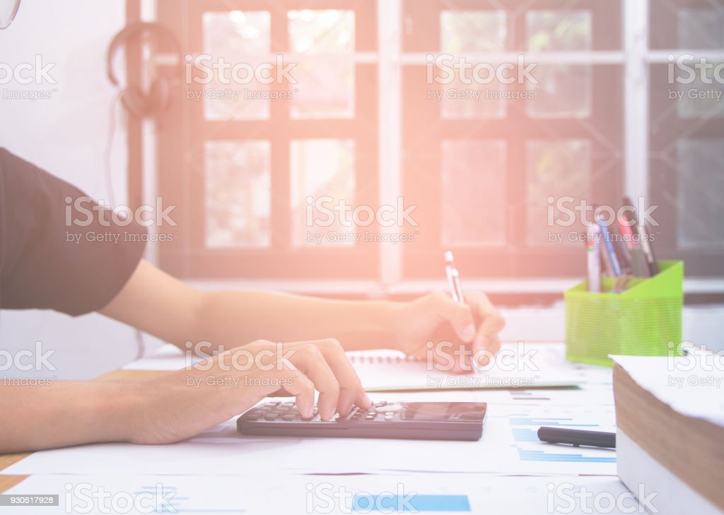 Business man or accountant in gray shirt holding pen working on accounts and using calculator and writing on desk, With sunset light. stock photo