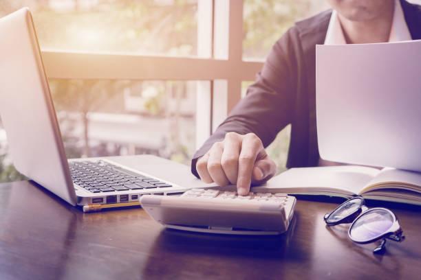 アカウントに取り組んでいるビジネス人または弁護士会計士電卓を使用して、ドキュメント、ペンとボタンを押して両手のラップトップ上に書き込むエンジニア リング ホーム計画 - パラリーガル ストックフォトと画像