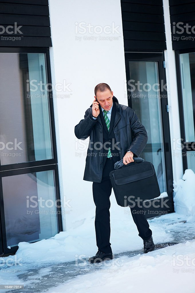 Business man outside stylish home in snow on the phone royalty-free stock photo