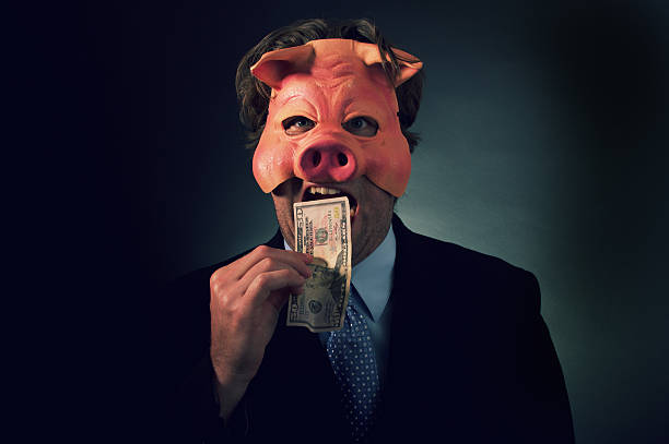Business Man Pig Eating Money a businessman wearing a pig mask eating money. greed stock pictures, royalty-free photos & images