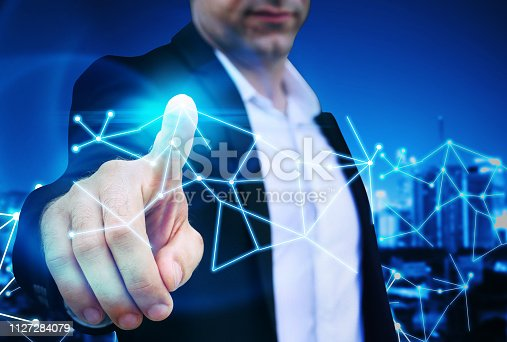 1155541483istockphoto Business man point finger to global futuristic technology network 1127284079