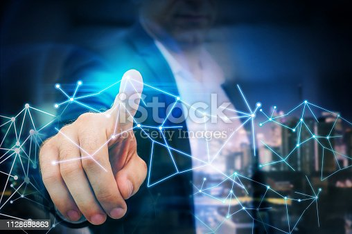 1155541483istockphoto Business man point finger to global futuristic technology network 1128698863