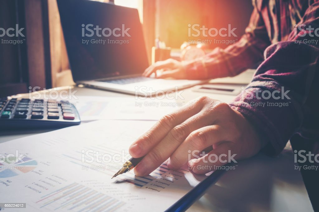 business man pointing his ideas and writing business plan at workplace,man holding pens and papers, making notes in documents, on the table stock photo