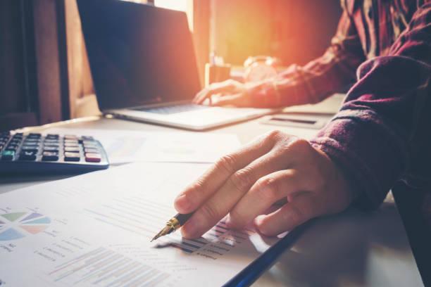 hombre de negocios apuntando sus ideas y escribir plan de negocios en el lugar de trabajo, corrales de hombre y papeles, hacer anotaciones en documentos, en la mesa - foto de stock