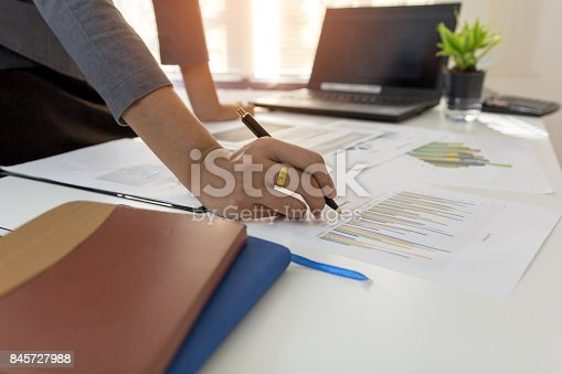 858031152istockphoto Business man pointing on data paper datawork on office table with laptop.Concept business and finance. 845727988