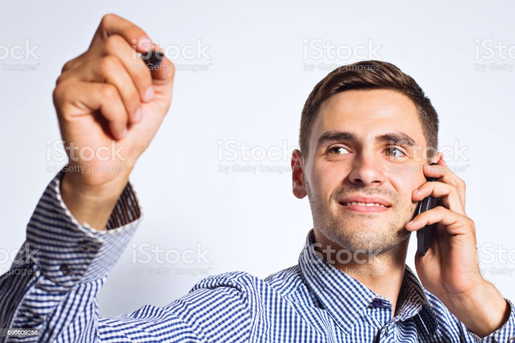 Business man pointing something with marker and mobile telephone on white background stock photo