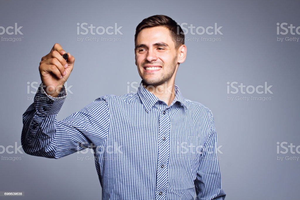 Business man pointing something with marker on gray background stock photo